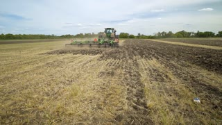 Ploughing field. Agricultural tractor plowing farming field. Farming tractor plowing arable field. Process plowing agricultural field. Farming equipment. Agricultural machinery