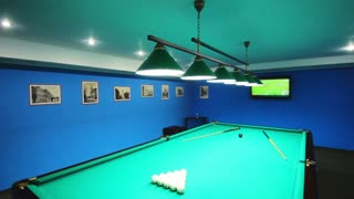 Pool game table. Empty paying room. Lighted billiard table green before game. Snooker ball and cues on table. Billiard balls on green pool table. Billiard room background. Billiard club
