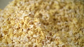 Pop corn background. Process of drying popcorn after manufacturing. Ready popcorn flakes in popcorn machine. Human hand pouring pop corn flakes by ladle. Process of pop corn production