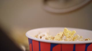 Popcorn flakes pouring by ladle to paper container in slow motion. Movie entertainment concept. Popcorn is ready for eating. Popcorn box full of fresh flakes