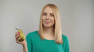 Portrait of blonde woman eat pear at white background. Close up of blond girl eating organic food at studio. Vegetarian woman biting ripe fruit
