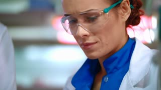 Portrait of woman scientist. Female scientist face in safety glasses. Close up of scientist woman speaking in lab. Lab woman face talking in lab. Female lab engineer portrait