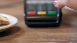 Pos terminal payment in cafe. Woman hand enter pin code on payment terminal. Banking services of electronic money. Credit card machine for money transaction. Closeup of female hand using bank terminal