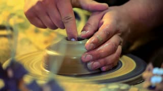 Potter make clay dishes. Master hands working on potters wheel. Traditional process making dishes on potters wheel. Close up of traditional making pottery on potters wheel