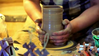 Potter making clay vase. Male potter make ceramic dishes. Close up traditional process of making clay dishes on potters wheel. Traditional process making clay pitcher on potter wheel