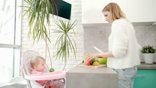Pretty woman cooking healthy food with baby. Mom preparing baby food. Mother cook healthy eating for little child in baby chair. Healthy diet for little child