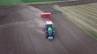 Process plowing agricultural field. Sowing machine working on cultivated field. Agriculture machinery. Sky view agricultural tractor with trailer seeder working on plowed land. Agricultural industry