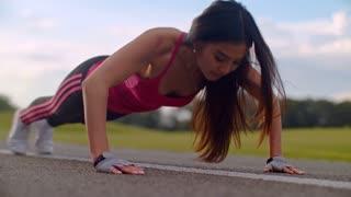 Push ups exercise. Push up woman. Closeup of asian woman pushing on road. Asian woman outdoor workout. Close up of slim woman push ups outdoors. Close up of attractive brunette push up on road