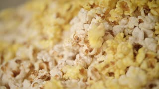 Ready popcorn falling in popcorn machine. Popcorn production process. Close up of process of pop corn production in slow motion. Cinema food background