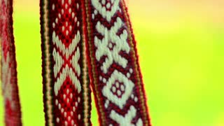 Red ribbon decoration with white slavic pattern. Slavic amulets with embroidered ethnic print. Traditional ribbons with ethnic white ornament. Close up ethnic bandages with geometric pattern