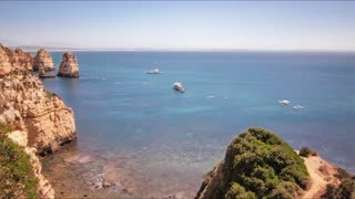 Rocky sea shore and sailing ships. Time lapse of cruise ships swimming in calm water. Sail ships at sea. Panoramic view sailing ships at sea. Sea ship near rocky coastline