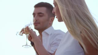 Romantic couple drinking champagne at sunset. Happy people celebrating anniversary. Love couple toasting champagne. Love couple romantic date