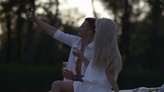 Romantic couple taking selfie photo in evening. Lovers capturing happy moments. Romantic date with champagne. Love couple posing for selfie. Happy love concept