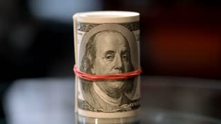 Rotating roll of hundred USA dollar bills with red rubber band. Cash money roll on table. Family savings concept. Starting investment capital. Exchange currency financial operations
