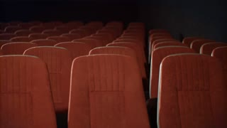 Rows of empty seats in cinema theatre. Empty armchairs in theatre. Red seats in movie theatre. Cinema chair before movie. Movie entertainment concept