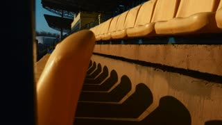 Rows of numbered plastic chairs in open football stadium. Close up empty yellow seats on grandstand. Olympic arena with tribune at daylight. Soccer stadium background. Sport competition place