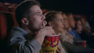 Rude man eating popcorn at cinema. Guy greedily eating pop corn in cinema in slow motion. Rude manners at movie hall