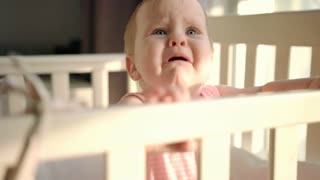 Sad baby crying in cot at home. Unhappy toddler standing in crib. Upset child in bed looking mom. Unhappy child wake up at morning. Sadness baby emotion. Child fear