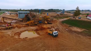 Sand extraction at quarry. Sky view of mining equipment working at industrial area. Mining truck moving at industrial territory sand mine. Mining conveyor pour sand at dumper truck. Aerial view