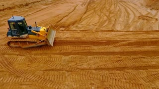 Sand mining industry. Bulldozer machine. Crawler bulldozer moving at sand mine. Mining machinery working at sand quarry. Drone view of mining equipment at industrial sand quarry. Earth mover