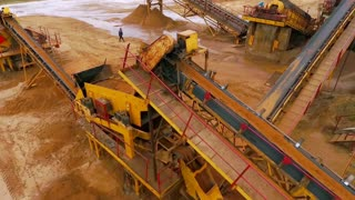 Sand moving on automatic conveyor belt. Mining conveyor sand sorting. Mining equipment at sand quarry. Mining machinery working at industrial area. Aerial view manufacturing line at mining sand
