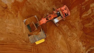 Sand work aerial view. Drone view of mining truck and excavator working at sand quarry. Mining excavator pouring sand in dump truck. Aerial view of mining equipment. Mining machinery at sand mine
