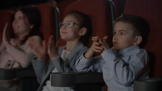 Satisfied children applauding in cinema. Storm of applause in cinema. Kids clap hands in cinema in slow motion. Happy children clapping hands at cinema. Happy kids like cartoon movie