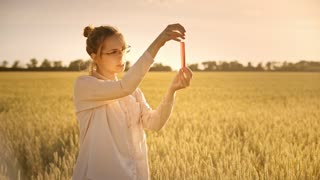 Science agronomist with lab flask in wheat field. Agriculture research. Biochemist analysing liquid sample outdoor. Agriculture science scientist working