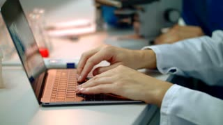 Scientist hand typing on laptop. Female scientist hands on laptop. Close up of woman hands typing on laboratory laptop. Closeup of female hands typing on scientist laptop