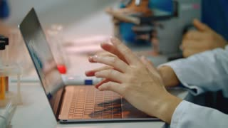 Scientist hands typing on laptop keyboard. Female doctor hand typing laptop. Laboratory woman typing on computer keyboard. Close up of female hands using laptop in lab. Female hands typing on laptop