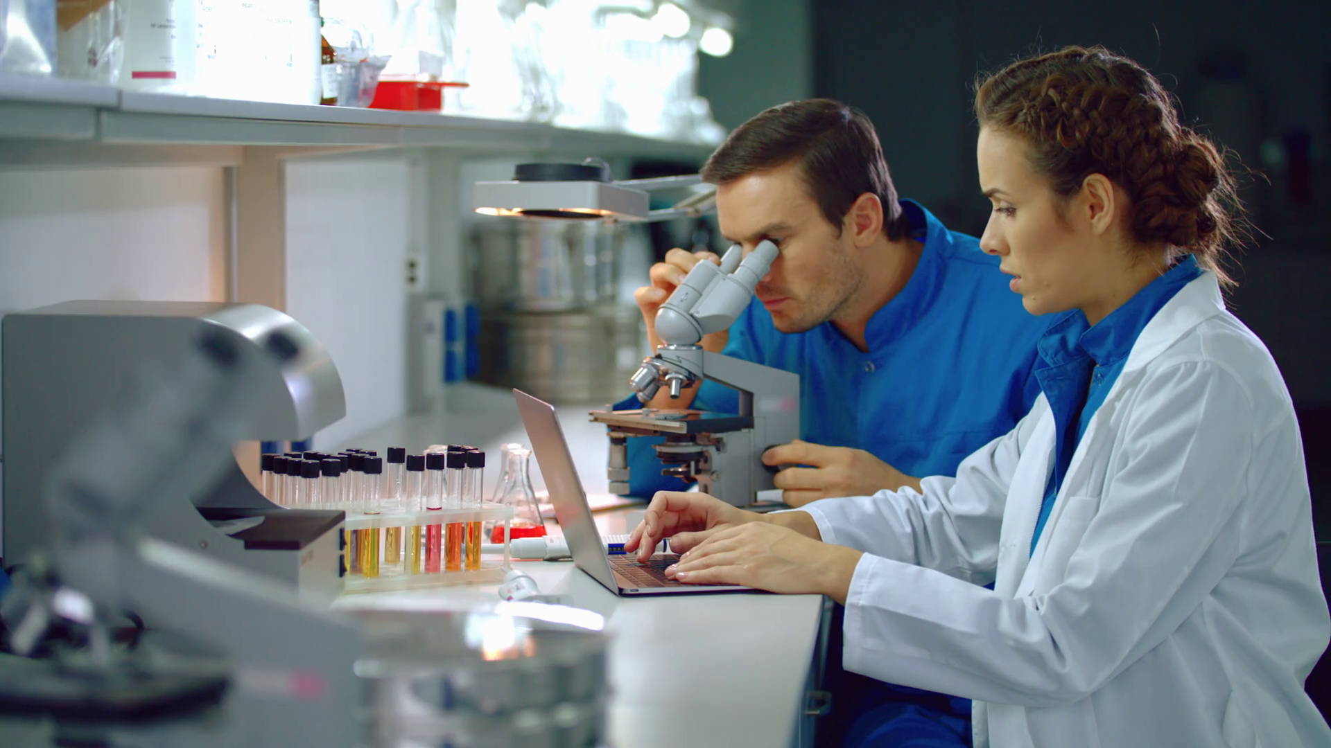 Scientist team working in lab. Laboratory team doing microscope research. Female and male scientist research microscope. Man scientist looking microscope in lab. Lab woman using scientist laptop Stock Video Footage - Storyblocks