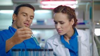 Scientist team working in lab. Scientist discussing liquid sample in test tube. Group of scientists in lab. Male and female scientist talking about science research result
