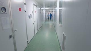 Scientists walking lab corridor. Pharmaceutical workers talking in laboratory corridor. Researchers talking in white corridor. Steady cam shot of scientists walking through laboratory corridor