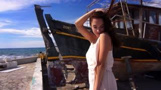 Sea model posing for camera on seashore. Beauty woman enjoy summer relax. Brunette girl touching hair. Sensual model near old ship. Sexy woman touching hair