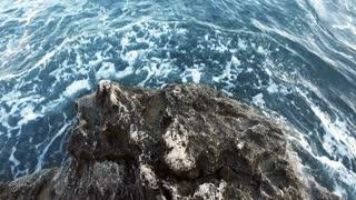 Sea wave crashing on rock coast pov. Close up of blue ocean breaking waves. Deep blue sea water beating of rocky coastline. Foamy surf on pebble beach. Waves breaking along shore
