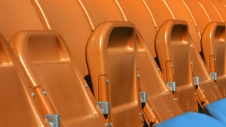 Seating rows in stadium with folded chairs. Close up empty orange and blue seats on grandstand. Open sports arena with tribune at daylight. Empty fans zone on soccer stadium. Football stadium chairs