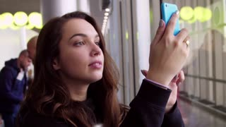 Self portrait of young woman on holidays. Brunette girl taking picture on smartphone at airport. Smiling girl posing for selfie. Girl take picture on mobile phone. Tourist making instagram photo