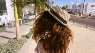 Sensual woman in hat walking in tropical city. Back view of walking girl in hat at Cyprus. Brunette woman walk in tropical city. Luxury girl enjoy summer walk
