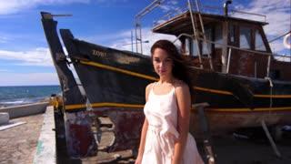 Sensual woman on sea coast enjoy windy weather. Brunette woman posing for camera near sea ship. Summer model on seashore. Female model near old ship. Beauty girl with wind hair
