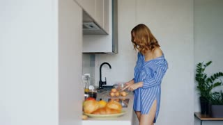 Sensual woman whisking eggs in glass bowl for cooking omelet. Cheerful woman preparing traditional morning breakfast in modern kitchen. Sexy girl in blue shirt cooking scrambled eggs. Breakfast eggs