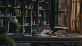 Serious business man reading documents at table. Young businessman signing documents at home office. Paperwork in creative studio. Business owner doing paper work