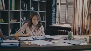 Serious businesswoman sitting at table and trying find solution of business problem. Worker woman doing market research. Tired employee analyse business data on document. Business woman thinking