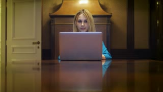 Serious woman working on notebook computer sitting at table in home studio. Business woman looking on laptop screen in luxury apartment