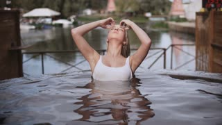 Sexy blonde woman in bath outdoor. Sensual woman enjoy relax in jacuzzi at luxury vacation. Beauty girl in white swimsuit enjoy bath in slow motion