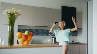 Sexy girl dancing in kitchen. Happy woman in underwear listening music at home. Young woman dancing with headphones and smartphone. Morning fun in modern kitchen. Dancing girl