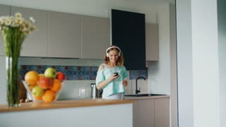 Sexy girl in underwear dancing in kitchen at home. Happy woman listening to music in headphones with smartphone in kitchen. Morning fun during breakfast time. Enjoying new great day concept