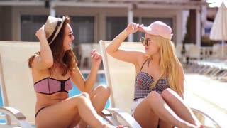 Sexy girls in swimsuit changing hats at summer pool. Pretty woman sunbathing on chaise lounge. Blonde and brunette girls trying hats. Chaise lounge relax. Enjoy summer holiday