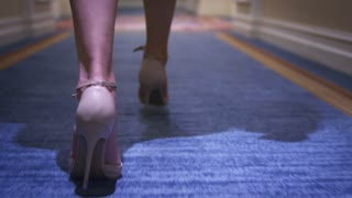Sexy woman in beige shoes walking on carpet floor back view. Close up female legs in high heeled shoes walking on long corridor
