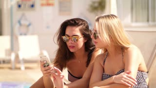 Sexy woman in sunglasses looking phone at beach. Summer girls holding mobile on sun bathing. Blonde and brunette woman look mobile phone at resort. Summer holiday. Sexy girls look smartphone