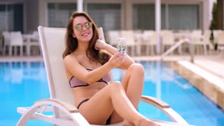 Sexy woman making selfie at swimming pool. Brunette woman woman taking selfie at chaise lounge. Summer girl enjoy resort relax. Pretty woman take a picture on mobile at beach